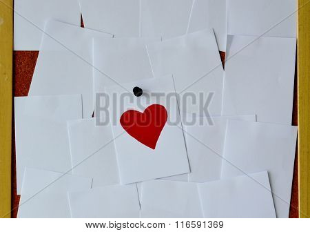 red heart paper note on wooden notice board