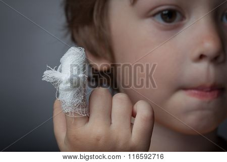 boy with a bandaged wound on his finger