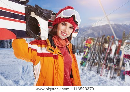 Female snowboarder on top of the winter mountain