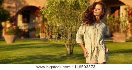 Spring woman in summer dress walking in green Italy garden enjoying the sun. sunny day.