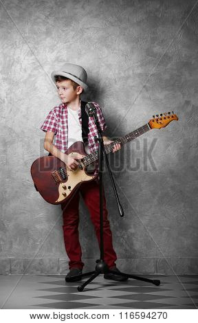 Little boy with guitar singing into the microphone on a grey wall background