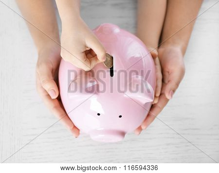 Savings concept. Hand putting coin in the piggy bank on wooden background