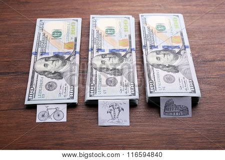 Stacks of money for different needs on wooden background