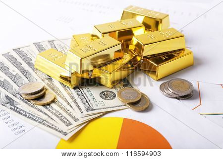 Gold bars with dollar banknotes and euro coins on paper background