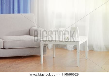 Sofa and little table with home decor in the room in front of the window with curtains