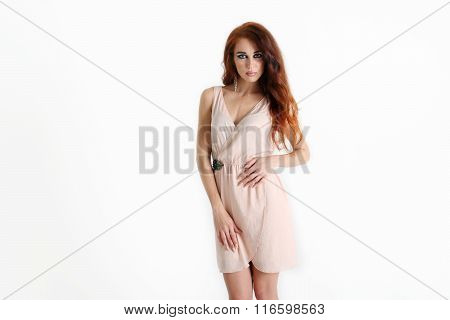 Standing Beautiful Young Girl With Red Hair With Short Beige Dress