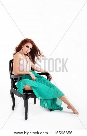 Seated On Chair Beautiful Young Girl With Red Hair Posing With In Green Skirt