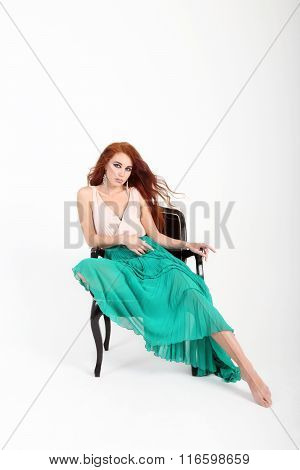 Seated On Chair Beautiful Young Girl Posing With In Green Skirt