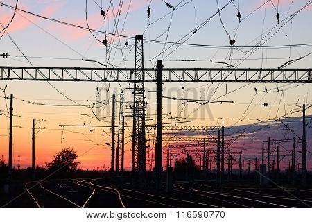 Rails Railway Line In Dark During Pink Sunset And Poles With Wires