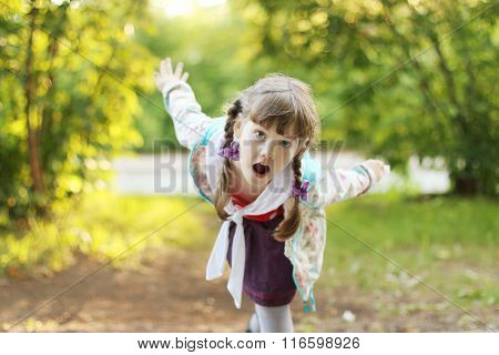 Pretty Smiling Little Girl With Braids Depicts Bird At Sunny Day. Shallow Dof