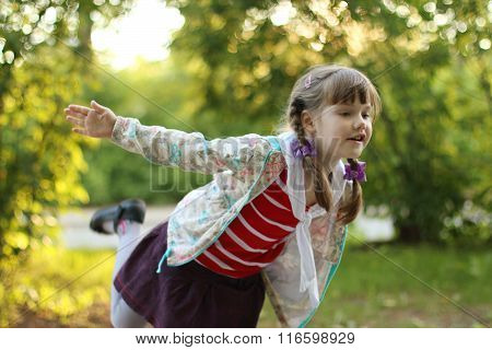 Beautiful Little Girl With Braids Depicts Bird At Sunny Day. Shallow Dof