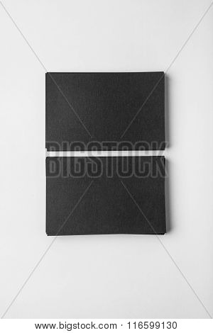 Two stack of blank black business cards on white background with soft shadows. Vertical