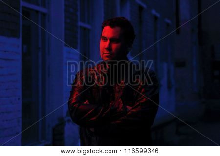 Beautiful Man In Leather Jacket Looks Away In Red Light At Night On Street