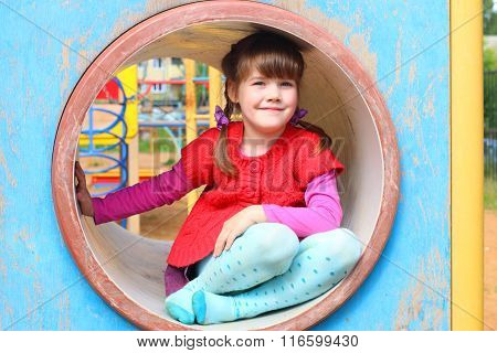Pretty Little Girl Sits In Pipe On Playground At Summer Day And Smiles