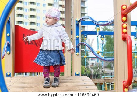 Pretty Little Girl In Hat Goes On Bridge On Playground At Summer Day