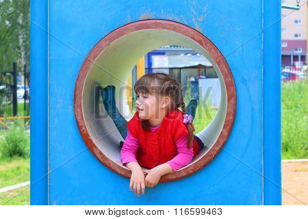 Pretty Little Girl Lies In Pipe On Playground At Summer Day And Smiles