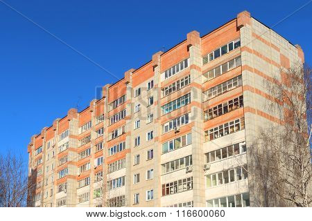 Top Of High Residential Building With Balconies And Trees At Sunny Winter Day