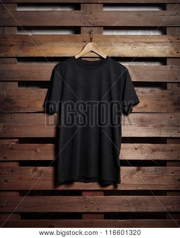 Photo of black tshirt holding on wood background