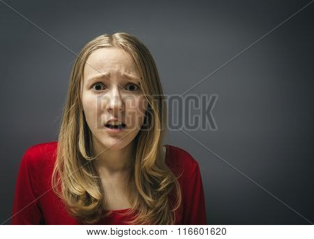 Portrait of a young girl in a red dress on a gray background. Frightened shocked scared woman