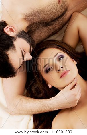 Relaxed young couple lying in bed.