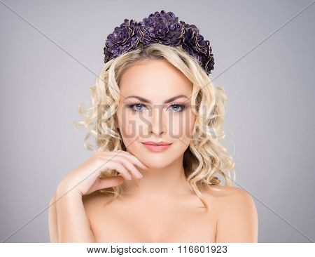 Gorgeous, elegant, sexy woman with bare shoulders wearing purple headband over grey background.