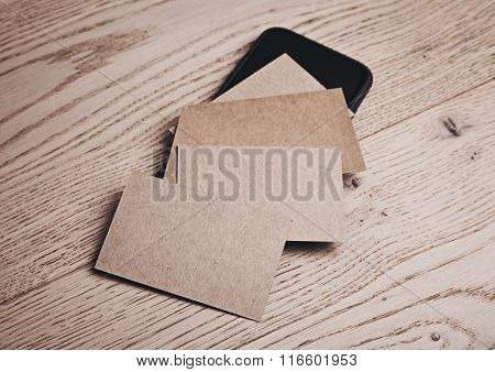 Set of blank business cards on wood table and smartphone. Horizontal
