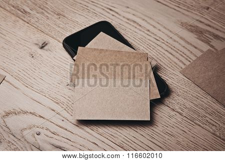 Set of blank business cards on wood table and smartphone under cards. Horizontal