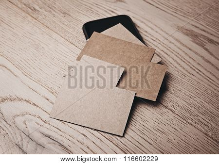 Set of craft business cards on wood table and smartphone under cards. Horizontal