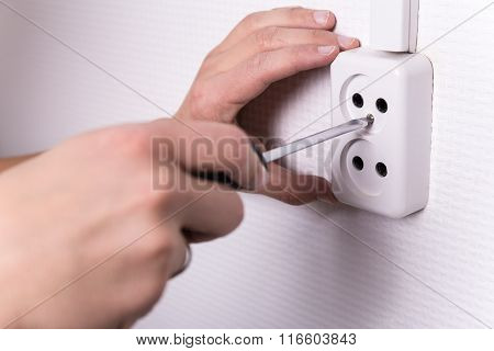 Male Hands With Screwdriver Installing Electrical Socket On Wall
