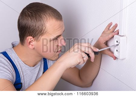 Young Electrician Installing Electrical Socket On Wall