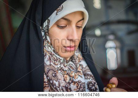 Beautiful Muslim young woman using tespih for praying