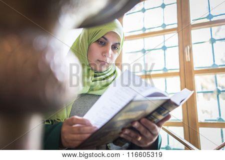 Beautiful Muslim young woman inside the mosque reading holy book Koran