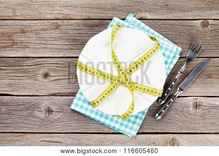 Healthy food concept. Plate, fork, knife and tape measure on wooden table. Top view with copy space