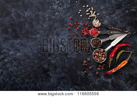 Colorful peppercorn and chili peppers on stone table. Top view with copy space