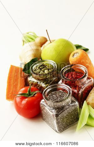 Super food - goji berries, chia seeds and pumpkin seeds with vegetables, fruits and herbs