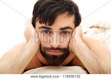 Depressed man in bedroom.