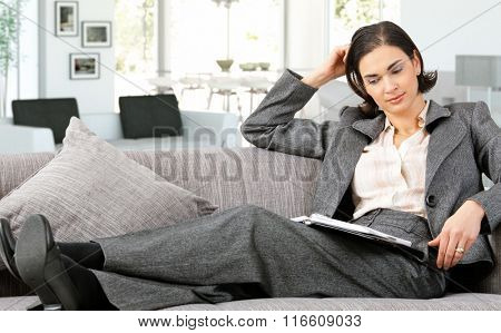 Mid adult caucasian businesswoman in suit lying on sofa with personal business organizer at home, thinking. Small smile.