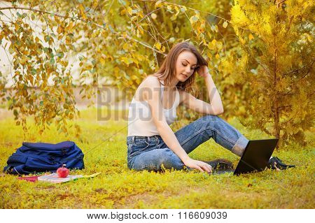 Student girl on grass with a computer