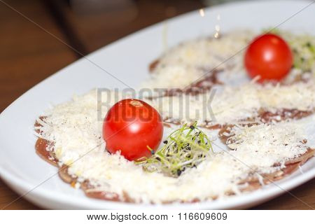 Appetizer carpaccio with Parmesan cheese, cherry tomatoes and sprouts.