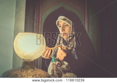 Beautiful Muslim young woman with a lamp