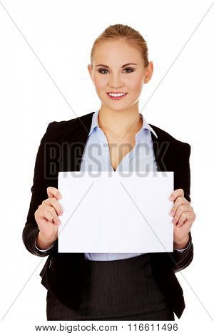 Smiling young businesswoman holding blank banner