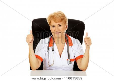 Smile elderly female doctor or nurse sitting behind the desk and shows thumbs up