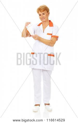 Smile elderly female doctor or nurse holds bandage