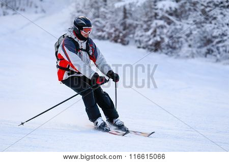 Skier skiing downhill in high winter mountains against sunshine. Male skier against a snowy background and pine trees, mountains.
