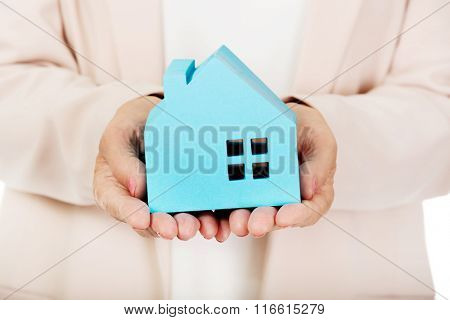 Elderly business woman holding blue paper house