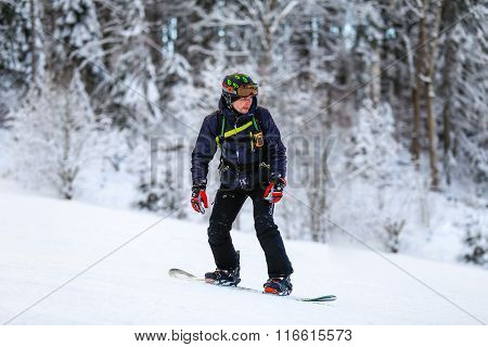 Snowboarder in black suit slides down