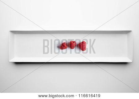 Three Raspberries Isolated On White Ceramic Plate