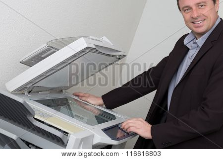 Cheerful Business Man With Arms On Printer Looking At The Camera
