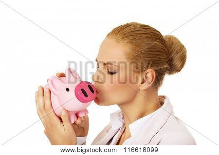 Young business woman kissing a piggybank