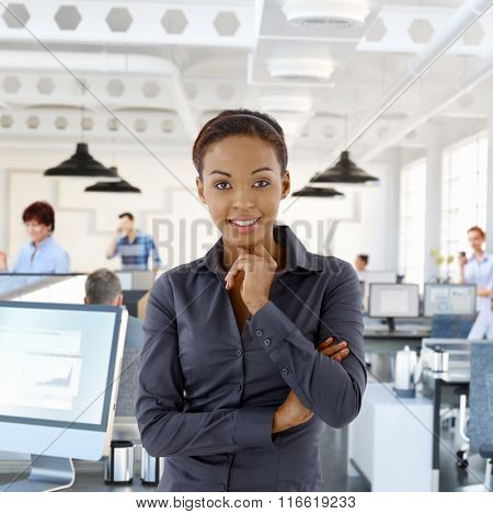 Portrait of happy black female office worker in office with working people.